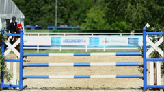 Horseman on horse jumps over barrier at competitions Stock Footage
