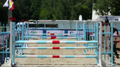Rider on horse jumps over three barriers at competitions - stock footage