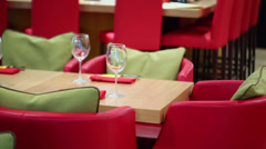 Red leather chairs stand near wooden tables and bar counter Stock Footage