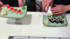 Two men prepares pair of plates with different rolls on table Stock Footage
