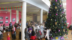 Parents taking kids to meet Santa in front of christmas tree Stock Footage
