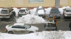 Man and buldo-excavator removing snow from the street Stock Footage