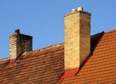 Two brick chimneys on terracotta rooftiles Stock Photos