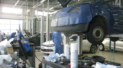 Mechanics working at cars in service at Volkswagen Center Stock Footage
