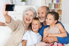 grandparents and grandchildren with a camera - stock photo