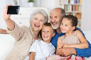 Stock Photo of grandparents and grandchildren with a camera