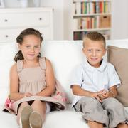 little brother and sister sitting on a couch - stock photo