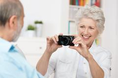 elderly woman photographing her husband - stock photo