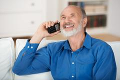 delighted senior man chatting on a mobile phone - stock photo