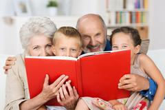 Grandchildren reading with their grandparents Stock Photos