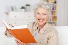 Stock Photo of smiling elderly lady reading a book