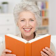 attractive senior woman reading a book - stock photo