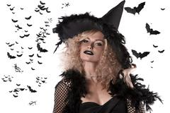 portrait of a curly blonde wearing a huge witch hat - stock photo