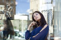 Young woman looking at shop window boutique Stock Photos