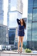 Stock Photo of sexy woman in a blue dress is stretching near skyscrapers
