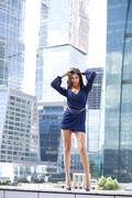 Sexy woman in a blue dress is stretching near skyscrapers Stock Photos