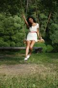 happy woman riding on a swing in the park - stock photo