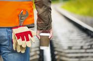 Stock Photo of Worker with a coffee on the rail