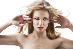 sensual pretty woman with flying hair, her both hands are open near the face - stock photo