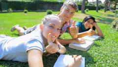 Three students in park laying happy thumb up back to school Stock Footage