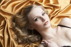 Portrait of blond woman laying, she looks in to the lens Stock Photos