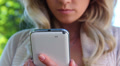Closeup of smiling blond girl writing message touch phone sms Footage