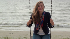 Girl swinging and laughing on a background of the sea Stock Footage