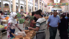 Veiled woman selling bread at bazaar in Tajikistan Stock Footage