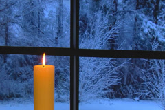 Glowing golden candle on snowy night in front of window Stock Footage