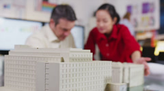 Cheerful architects or engineers looking at concept models of new development - stock footage