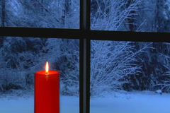 Red candle on snowy night in front of window Stock Footage