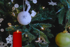 Red holiday candle with Christmas tree decorations in background - stock footage