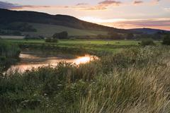 Summer sunset reflected in river in countryside landscape during late summer Stock Photos