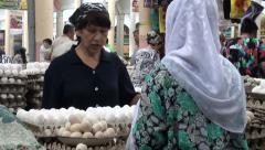Muslim woman selling eggs to a customer at Khujand bazaar Stock Footage