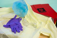 disposable hospital gown, gloves, hair cover and goggles next to a biohazard - stock photo