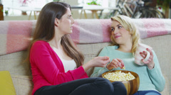 Young girlfriends gossiping together as they relax at home - stock footage