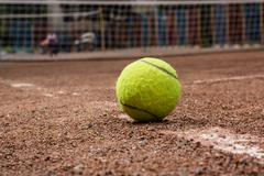 Tennis ball on a red court Stock Photos