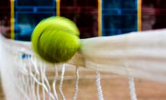 Flying tennis ball and a white net Stock Photos