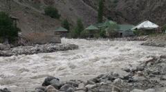 Raging river next to 'resort' in Tajikistan Stock Footage