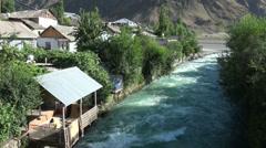 Restaurant along fast flowing stream in Tajik village Stock Footage