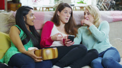 Young girlfriends gossiping together at home with popcorn - stock footage