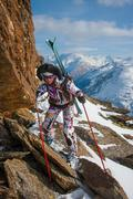 Woman with skis behind the rocks Stock Photos
