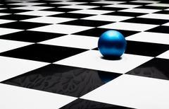 Blue ball on a checkered floor Stock Photos