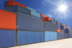 stack of cargo containers at container yard with sunbeam - stock photo