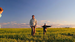 women and two children frolic, jump, whirl in a meadow on the green grass - stock footage