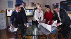 Attractive mixed ethnicity business team looking at a map of the world Stock Footage