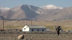 Woman carries buckets of water in poor Tajik settlement Stock Footage