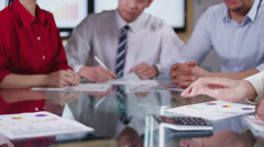 Business team in meeting, hands reach across the table to shake hands on a deal Stock Footage