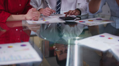 Business team in meeting, hands reach across the table to shake hands on a deal - stock footage
