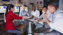 Diverse business group discuss profits & loss in a boardroom meeting - stock footage